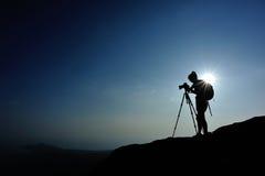Frauenphotograph, der Fotos an der Bergspitze macht Lizenzfreie Stockfotos