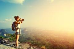 Frauenphotograph, der Fotos an der Bergspitze macht Lizenzfreies Stockbild