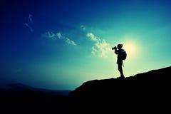 Frauenphotograph, der Fotos an der Bergspitze macht Lizenzfreie Stockfotografie