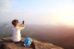 Frauenphotograph, der Fotos an der Bergspitze macht Stockfotografie