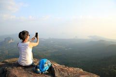 Frauenphotograph, der Fotos an der Bergspitze macht Lizenzfreies Stockfoto