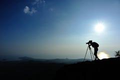 Frauenphotograph, der Fotos an der Bergspitze macht Stockbilder