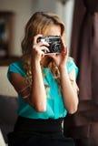 Frauenphotograph, der zuhause Fotos mit Retro- Filmkamera macht Lizenzfreie Stockfotos