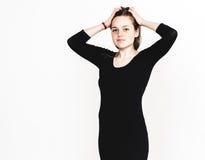 Frauenporträt im schwarzen Kleiderstudio, das mit dem langen Haar attraktiv aufwirft Stockbilder