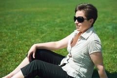Frauenporträt im Sommer im Freien, sitt auf grünem Gras, glückliche Menschen, Stadtpark stockfotografie