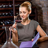 Frauenprobierenwein im Keller stockfoto