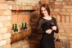 Frauenprobierenwein im l?ndlichen H?uscheninnenraum lizenzfreie stockbilder
