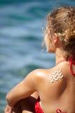Frauenrückseite mit Sonnenbrand und Welle der Sonnenlotion Stockfotos