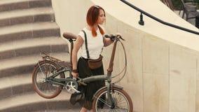 Frauenradfahrer, der hinunter Treppe geht und Fahrrad in den Armen hält Frauenfahrradstadt lizenzfreies stockbild