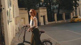 Frauenradfahrer, der neben Reitfahrrad auf Stadtstraße geht Frauenfahrradstadt lizenzfreies stockfoto