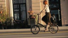 Frauenradfahrer, der neben Reitfahrrad auf Stadtstraße geht Frauenfahrradstadt lizenzfreie stockfotografie