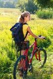 Frauenradfahrer mit Fahrrad und Rucksack Lizenzfreie Stockfotos