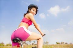 Frauenradfahrer-Reitenfaltendes Fahrrad und zurück schauen Stockbild