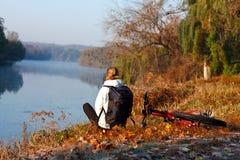 Frauenradfahrererholung auf dem Flussufer Lizenzfreie Stockbilder