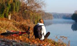Frauenradfahrererholung auf dem Flussufer Stockfoto