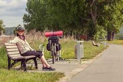 Frauenradfahrerreisender, der auf der Bank sitzt Stockbilder