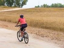 Frauenradfahrerreiten auf der Straße Lizenzfreie Stockbilder