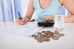 Frauenrechenrechnung durch Münzen und Thermostat am Schreibtisch Lizenzfreie Stockfotos