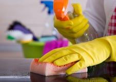 Frauenreinigung mit Schwamm und flüssigem Reinigungsmittel Lizenzfreies Stockfoto