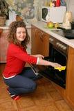 Frauenreinigungs-Kücheofen Stockfoto