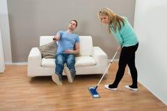 Frauenreinigungsboden während Mann auf Sofa Stockbilder