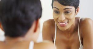 Frauenreinigungsgesicht mit Wasser und Schauen im Spiegel Stockbild