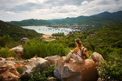 Frauenreisender betrachtet Rand der Klippe auf Seebucht von mounta Lizenzfreie Stockfotografie