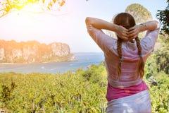 Frauenreisender, der Ansicht des Strandes und des Meeres von der Spitze eines Berges in den Dschungeln genießt stockfoto