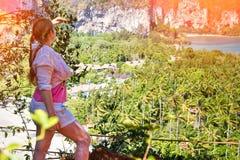 Frauenreisender, der Ansicht genie?t und weit weg auf Dschungel und Meer von der Spitze des H?gels schaut stockfotos