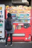 Frauenreisender, der ein Getränk vom Automaten kauft stockfotos