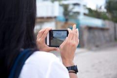 Frauenreisender, der Foto des Strandes mit Handy macht Lizenzfreie Stockbilder