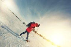 Frauenreisender in der hellen Winterjacke geht auf ein schneebedecktes Feld an einem sonnigen Tag Stockfoto