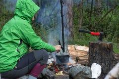 Frauenreisender, der Lebensmittel im Kessel auf Feuer im Wald kocht Lizenzfreie Stockfotos