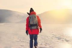 Frauenreisender geht auf schneebedeckte Wüste bei Sonnenuntergang Blendenfleckeffekt Lizenzfreies Stockfoto