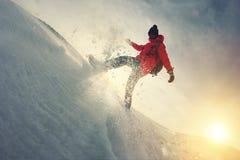 Frauenreisender geht durch den Schnee Schnee fliegt von unterhalb seiner Füße Stockbild