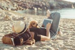 Frauenreisender hält Notenauflage, während entspannendes Freien während seiner Reise auf dem Meer ist lizenzfreie stockfotografie