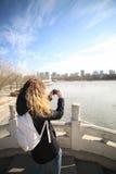 Frauenreisender macht ein Foto der Landschaft der Stadt nahe dem See im Park Lizenzfreies Stockbild