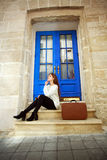 Frauenreisender mit einem Koffersitzen träumerisch an ihrem Haus Stockbilder