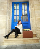 Frauenreisender mit einem Koffersitzen träumerisch an ihrem Haus Lizenzfreies Stockbild