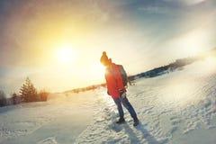 Frauenreisender mit einem Rucksack betrachtet seine Bahnen im Schnee Stockfoto
