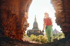 Frauenreisender mit einem Rucksack gehend durch das alte Bagan, welches die alten buddhistischen stupas schaut myanmar lizenzfreie stockfotos