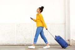 Frauenreisender mit Gepäck und Handy stockfoto