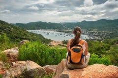 Frauenreisender sitzt und betrachtet den Rand der Klippe auf dem s stockfotografie