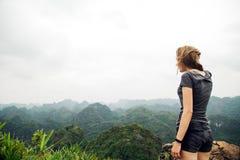 Frauenreisender steht auf einen Berg und bewundert die begeisterte Landschaft lizenzfreies stockfoto