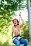 Frauenreiten auf einer Ziplinie stockfoto