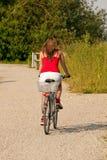 Frauenreiten ihr Fahrrad am Sommer Lizenzfreie Stockfotografie