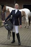 Frauenreiter-Holdingsattel auf ihrer Hüfte mit Pferd im Hintergrund Lizenzfreie Stockfotografie
