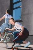 Frauenreitfahrrad und Schleppen ihrer lächelnden Freundin lizenzfreie stockbilder