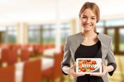Frauenrestaurantmanager, der Tablette mit Menü hält Lizenzfreie Stockbilder