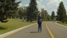 Frauenrolle, die rückwärts entlang Parkgasse reitet stock footage